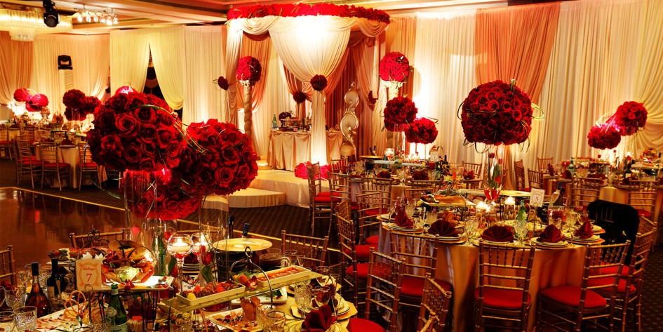 table-decorations-for-wedding-reception-with-red-flowers-in-glass-stand-vases-and-small-candles-holders-945x473